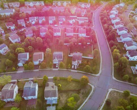 Aerial view over suburban homes and roads early sunrise