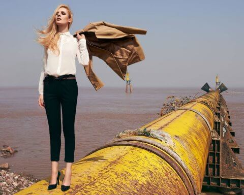 Fashionable woman standing on pipeline